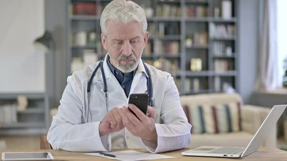 Senior Old Doctor Using Smartphone in Clinic
