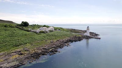 A Lighthouse on an Island with a Jetty and Ferry