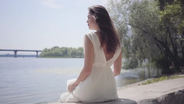 Cover Image for Portrait Charming Young Girl with Long Brunette Hair Wearing a Long White Summer Fashion Dress