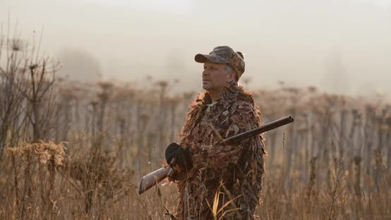 Cover Image for Portrait of Hunter with Shot Gun Standing in the Field and Looking Around, Foggy Autumn Morning