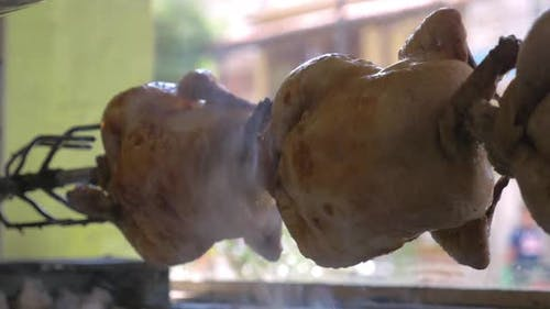 Close-up Shot of Cooking Appetizing Chicken on a Spit with a Light, Fragrant Smoke