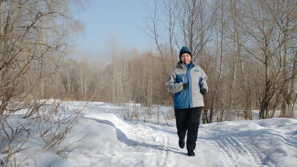 Thumbnail for Mature caucasian woman running in the forest on the snow
