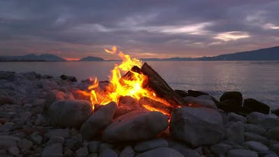 View of campfire on side of lake