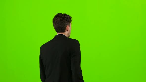 Thumbnail for Businessman Is a Telephone Rings To Him and He Talks. Green Screen. Back View