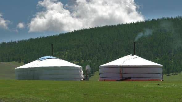 Mongolian tents with smoke from the chimney in front of the Taiga forests