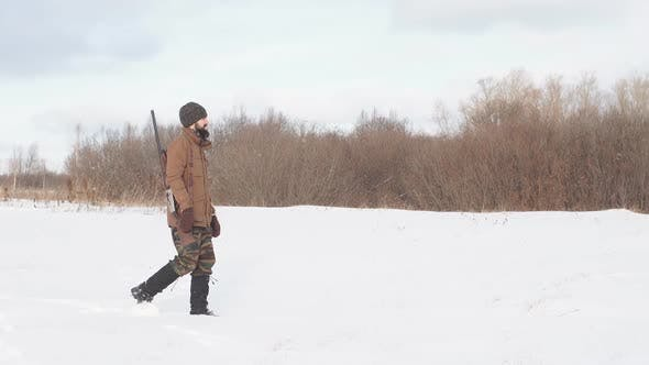 Thumbnail for Male Warm Clothes Walking on the Field with Hunting Rifle.