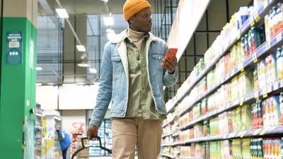 African American Guy Walks Along Grocery Shop and Types