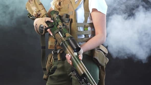 Young Blonde Female Snipper in Military Outfit with Assault Rifle in Studio. Slow Motion