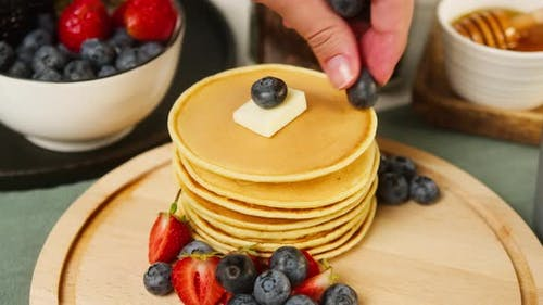 Decorating Buttermilk Pancakes with Berries on Top Closeup