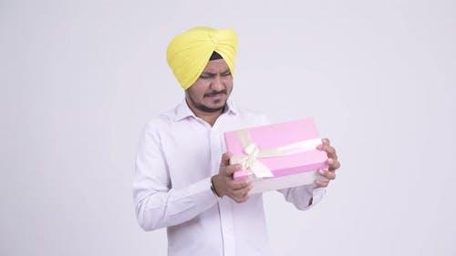 Bearded Indian Sikh Businessman Shaking Gift Box