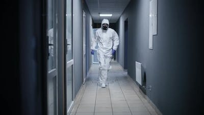 Men in Hazmat Suit Running Through a Corridor