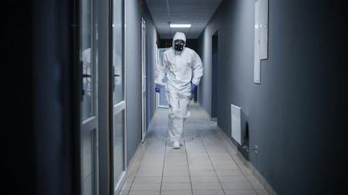 Men in Hazmat Suit Running Through a Corridor