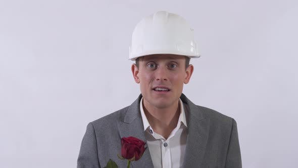 Thumbnail for Portrait of Genuine Shy Man in Helmet Extends a Hand Forward Holding Red Rose