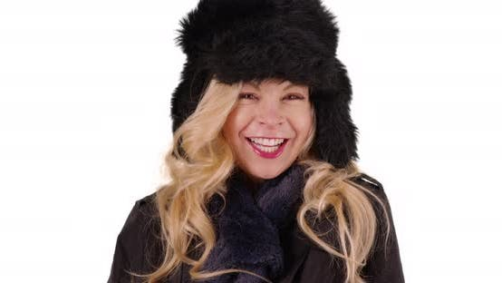 Thumbnail for Close up of cheerful woman in cozy fur hat and scarf smiling at camera in studio
