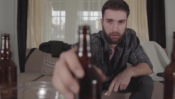 Thumbnail for Young Bearded Man Sitting on the Sofa Takes Empty Beer Bottle From the Table and Look at It with