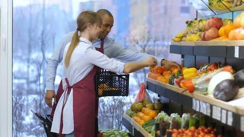 Shop Assistants Arranging Fruits in Supermarket
