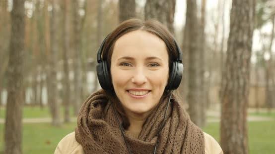 Portrait of woman put on headphones and listening to music. Girl enjoying music in earphones