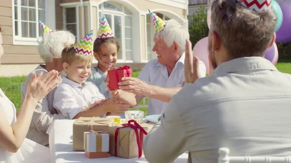 Thumbnail for Grandfather Receiving Birthday Gift from Family on Outdoor Party