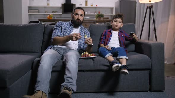 Cover Image for Relaxed Father and Son Watching Movie on Tv