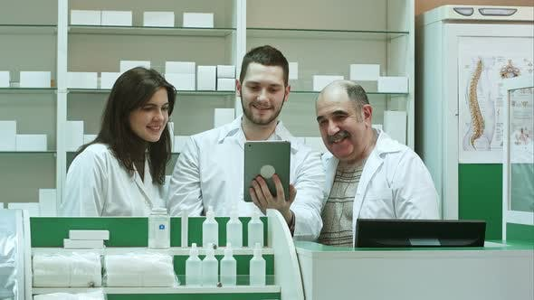 Competent Pharmacy Team with Pharmacist and Pharmacy Technicians Having Video Chat with Colleagues