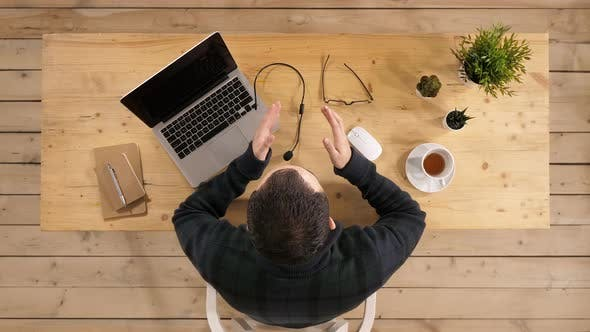 Thumbnail for Handsome Young Businessman Sitting at Office Desk with Laptop Computer and Talking To Someone