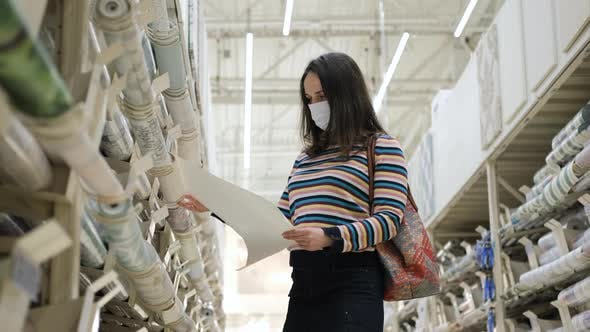 Woman Holding Roll of Wallpaper in a Store