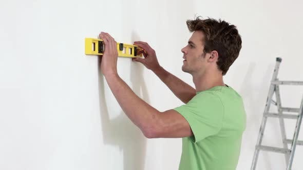 Thumbnail for Young man using spirit level on wall