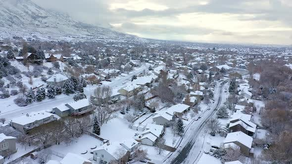 Aerial view flying over snow covered neighborhood in winter