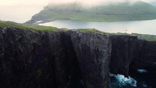 Aerial view of tourists English Slave cliff on North Atlantic sea, Faroe island.