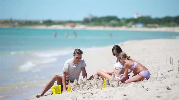 Thumbnail for Father and Kids Making Sand Castle at Tropical Beach. Family Playing with Beach Toys