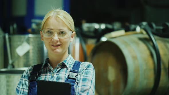 Portrait of a Laboratory Assistant Woman in Protective Glasses on the Background of Wine Barrels