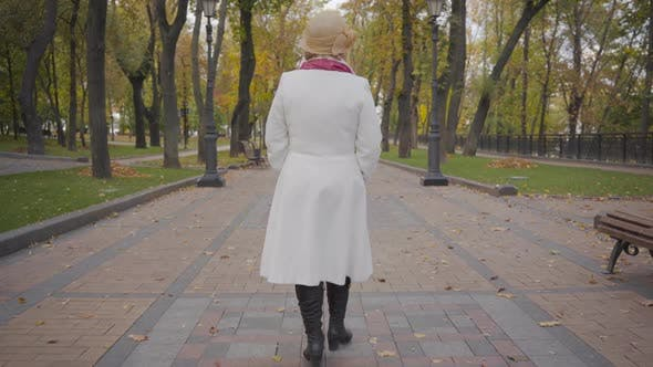 Thumbnail for Back View of Caucasian Woman in Elegant Beige Cloche Hat and White Coat Strolling Along the Alley