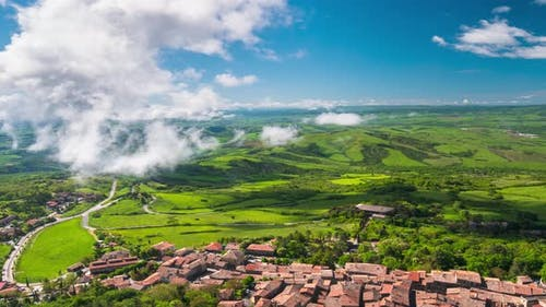 Time lapse aerial: unique green landscape in Orcia Valley, Tuscany, Italy. Scenic clouds moving by w
