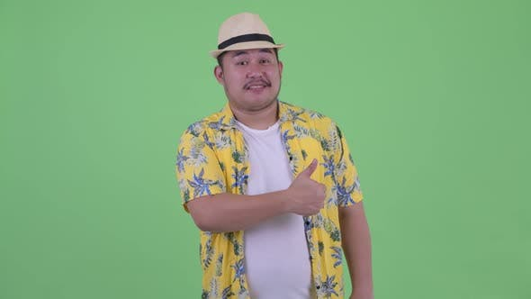 Thumbnail for Happy Young Overweight Asian Tourist Man Giving Thumbs Up