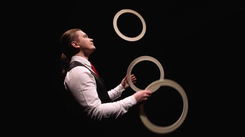 Camera Rotates Around Concentrated Man Juggling White Rings Then Puts Them Around His Neck