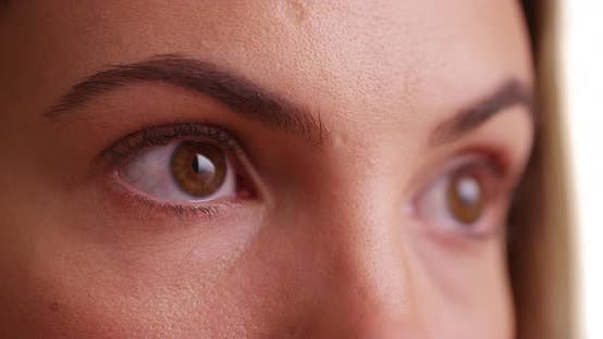 Thumbnail for Close up of female millenial's eyes looking off camera on white background