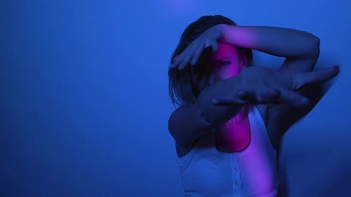 Beautiful Model Dancing in Dark Room with Pink Light Moving Around