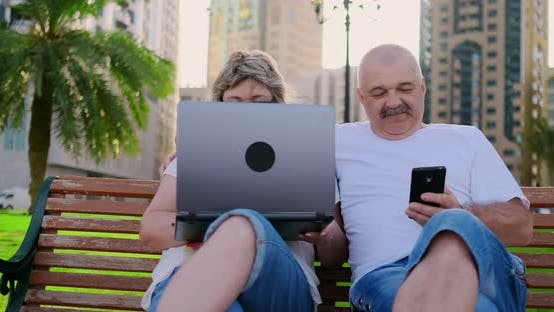 Cover Image for Happy Senior Couple Sitting on a Bench in the Summer in a Modern City with a Laptop