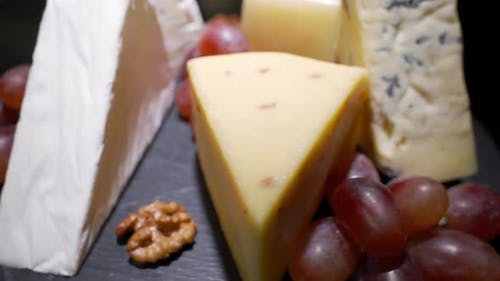 Cheese Plate Close-up with Several Varieties of Fruit and Honey Cheese