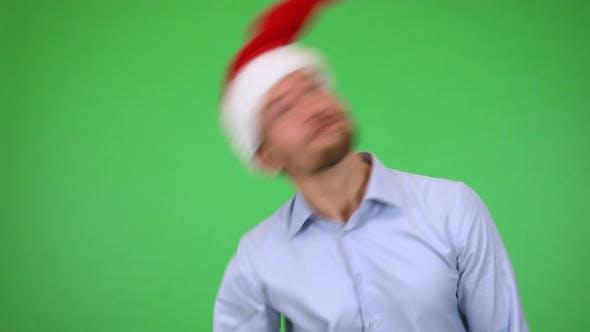 Thumbnail for Ein junger gutaussehender Mann dreht seine Weihnachtsmütze, dann lächelt bei der Kamera - Green Screen Studio