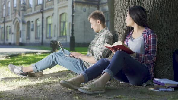 Thumbnail for Asian Girl Reading Book Under Tree and Looking at Guy Using Laptop Shyness