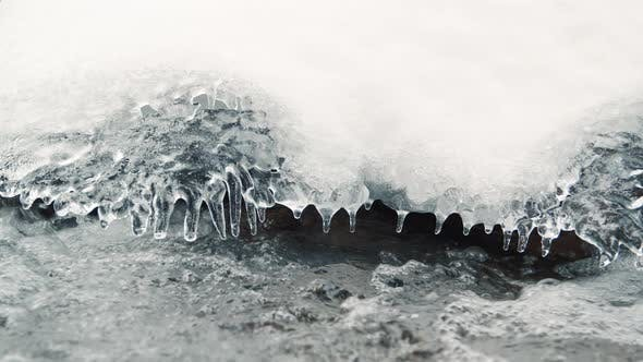 Thumbnail for Icicles Hanging From Powder Snow Over River Water Slow Motion