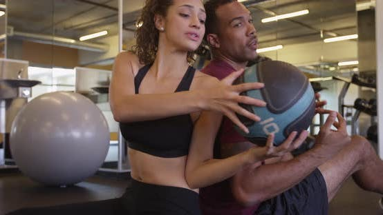 Thumbnail for Happy fit healthy Black and Hispanic couple passing medicine ball back and forth in gym working out