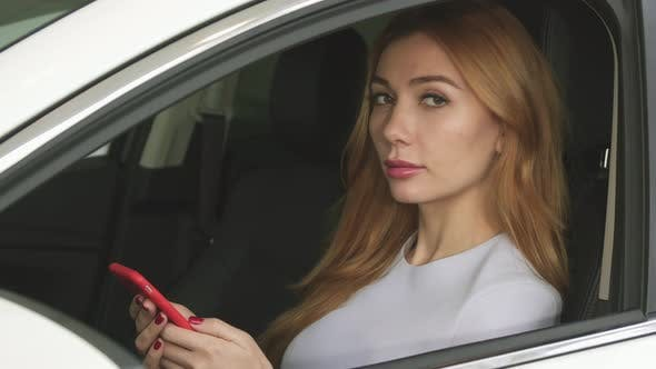 Thumbnail for Beautiful Young Woman Using Smart Phone Sitting in Her Car