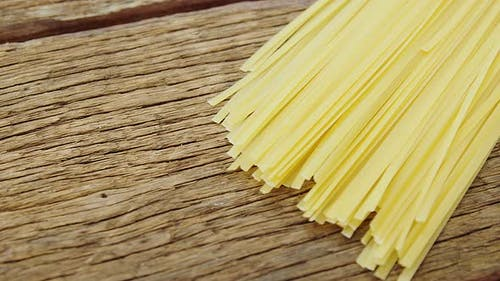 Uncooked tagliatelle pasta on wooden table background