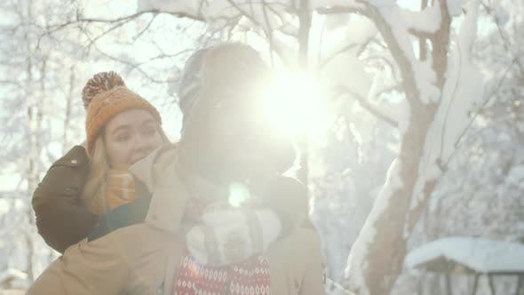 Man Giving Piggyback Ride to Happy Girlfriend in Snowy Park