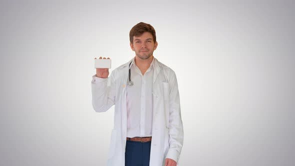 Smiling Male Doctor with Stethoscope Walking and Advertising Pills on Gradient Background
