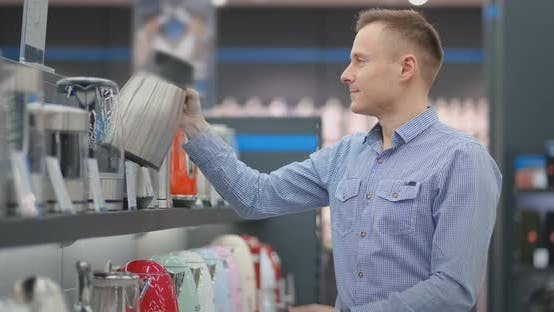 Thumbnail for Young Handsome Man Chooses an Electric Kettle To Buy. Inspects the Device, Examines the Price Tags