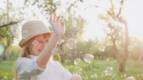 Cover Image for A Cheerful Girl in a Hat Carelessly Plays with Soap Bubbles. Happy Spring and Good Weather