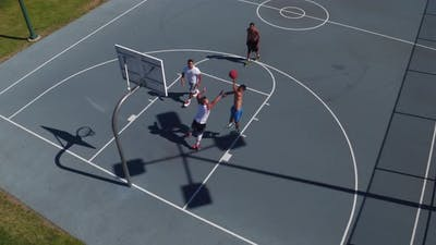 Friends playing basketball at park, high angle shot